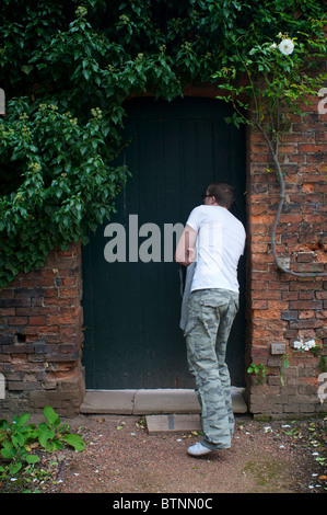 Young man looking through keyhole of garden door - Stock Photo