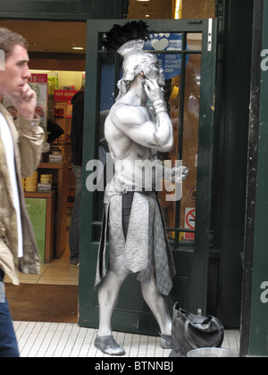 On the street in Covent Garden. Mime artist putting on his make up to be a roman soldier - Stock Photo