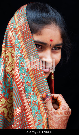Indian girl wearing traditional silk sari with henna hands. Face portrait. India - Stock Photo