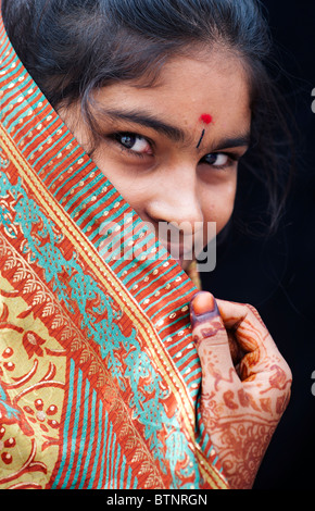 Indian girl wearing traditional silk sari with henna hands. India. Face portrait - Stock Photo