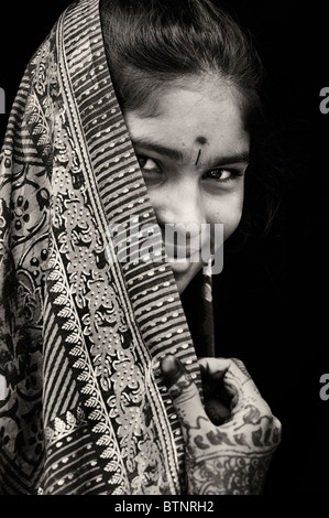 Indian girl wearing traditional silk sari with henna hands. India. Face portrait. Sepia tone - Stock Photo