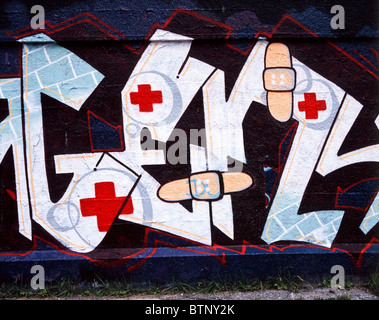 Graffiti showing red crosses and plasters / adhesive tapes on a wall in Munich, Germany - Stock Photo