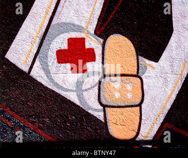 Graffiti showing a red cross and a plaster / adhesive tape on a wall in Munich, Germany - Stock Photo