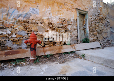 Fire hydrant against an old, decrepit stone wall in Ermoupolis, on the Greek Cyclade island of Syros. - Stock Photo