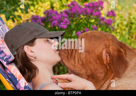Young girl and her big dogue de bordeaux in the garden - Stock Photo