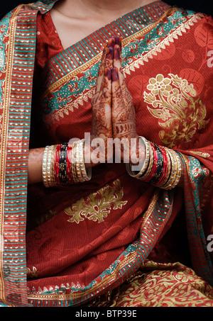 Indian girl wearing traditional silk sari with henna prayer hands. India - Stock Photo