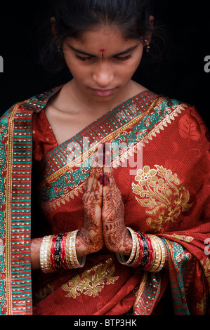 Indian girl wearing traditional silk sari with henna prayer hands - Stock Photo