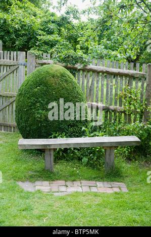 Bench in garden, Dorset, UK. - Stock Photo