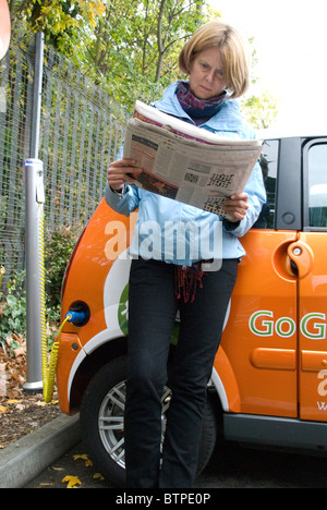 Woman reading paper waiting for car to charge Electric Cars free EV Elektrobay charging point Sainsbury's London - Stock Photo