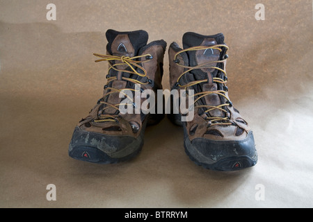 A pair of worn out lace up hiking boots. - Stock Photo