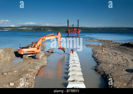 Large digger building sea defences at Dunoon, Argyll. - Stock Photo