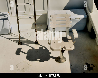 deep sea fishing boat with ladder and seat on deck with shadows - Stock Photo