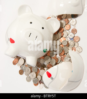 Broken Piggy Bank with coins flowing out - Stock Photo
