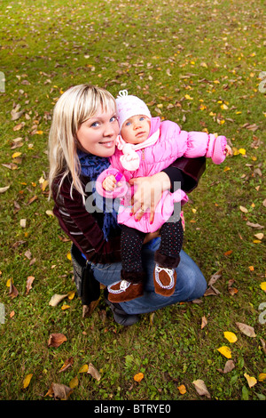 Young mother and little child siting on grass in autumn park. - Stock Photo