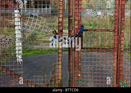 A chained up entrance gate to the wasteland site of a bankrupt business in the recession - Stock Photo