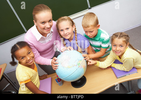 Portrait of pupils and teacher looking at camera with globe on table during geography lesson - Stock Photo