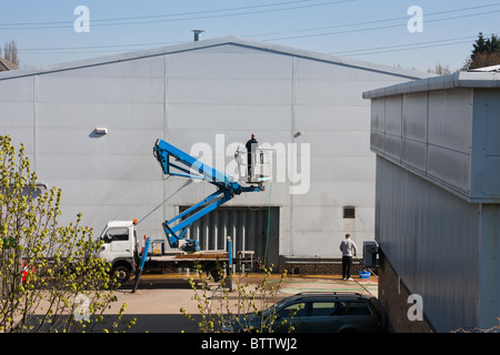 Men cleaning side of a building on a sunny day in London, England. - Stock Photo