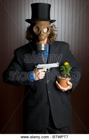 Businessman wearing a gas mask holding a gun to a flower - Stock Photo