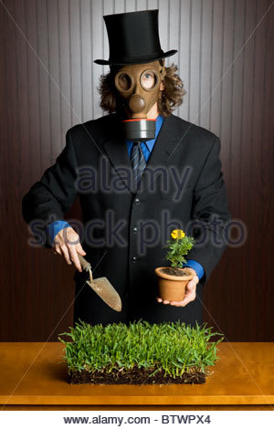Businessman wearing a gasmask holding a potting shovel and a flower standing over a patch of grass - Stock Photo
