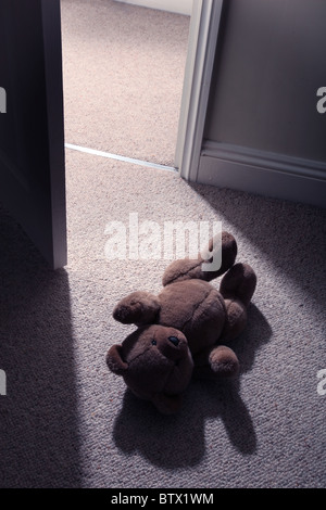 Man's legs and feett stepping past a child's teddy bear on the floor to leave the room. - Stock Photo