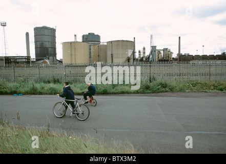 Two boys cycling past Redcar Steelworks, Teesside - Stock Photo