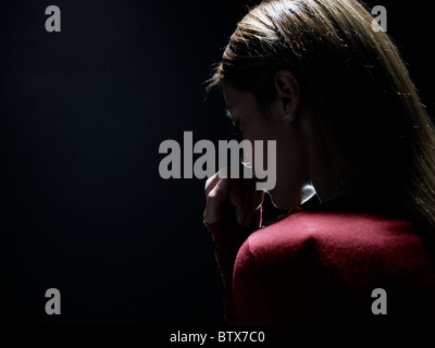 pensive woman on black background, representing the concept of anonymity - Stock Photo