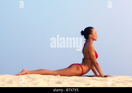 Image of female in red bikini sunbathing on sandy beach during vacation - Stock Photo
