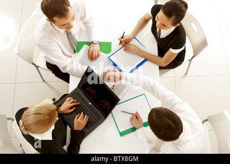 View from above of happy partners shaking hands at meeting - Stock Photo
