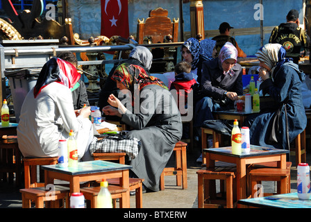 ISTANBUL, TURKEY. Turkish girls eating balik ekmek (fish sandwiches) by the ferry terminal in Eminonu district. - Stock Photo