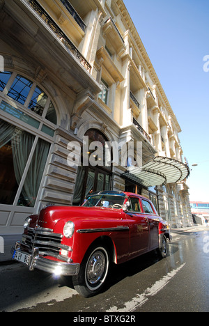 ISTANBUL, TURKEY. The Pera Palas Hotel in Beyoglu district, with one of the hotel's classic Plymouths parked outside. - Stock Photo