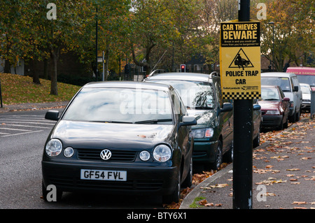 Sign warning of the use of a Police Trap Car in an attempt to deter car thieves - Stock Photo