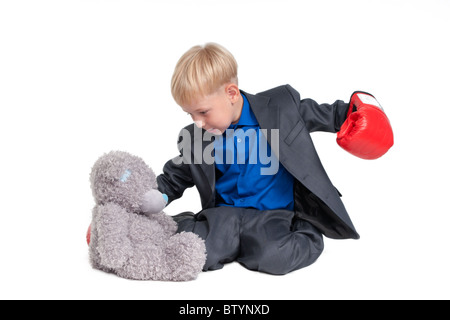 Blond boy in suit and boxer glove hitting a teddy bear - Stock Photo