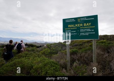 Back view of hikers walking along a rugged coastal pathway - Stock Photo