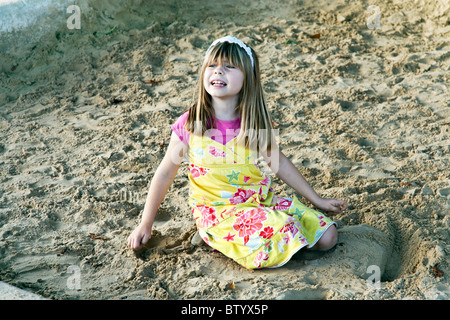 pretty little French girl in flowered yellow dress playing in sandbox in Notre Dame Cathedral park on a lovely autumn - Stock Photo