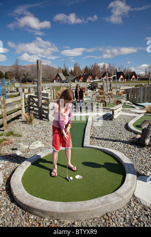Young girl playing mini golf, Twizel, Mackenzie Country, Canterbury, South Island, New Zealand - Stock Photo