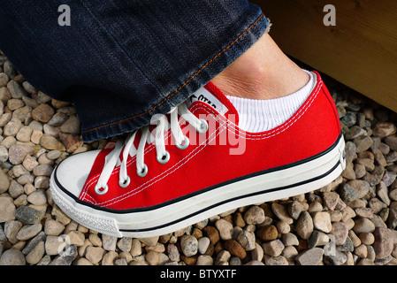 Single female red canvas sneaker. - Stock Photo