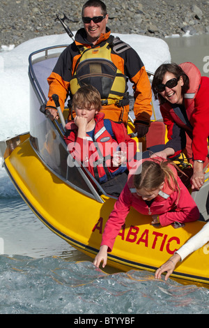 Tourist touching 300 year old iceberg from Glacier Explorers boat, Tasman Glacier Terminal Lake, Aoraki / Mt Cook - Stock Photo
