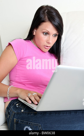 Shocked and surprised young woman looking at laptop screen - Stock Photo