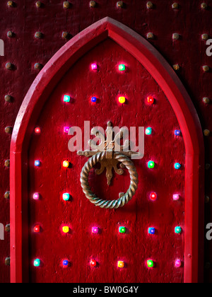 CHRISTMAS DOOR LIGHTS Old red wood Gothic door with number '25' and festive party lights at traditional Christmas - Stock Photo