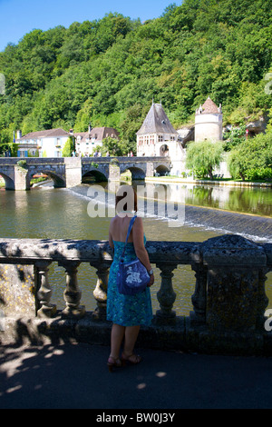 An attractive woman looking over a balustrade towards the River Dronne bridge and weir at Brantome, Dordogne, France, - Stock Photo