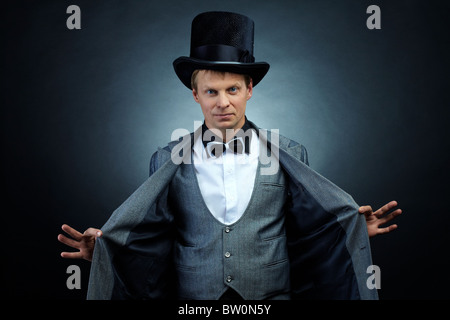 Image of male magician in hat and tail-coat looking at camera - Stock Photo