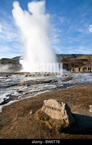 Tourists watching the eruption of Strokkur a geyser in southwest Iceland. - Stock Photo