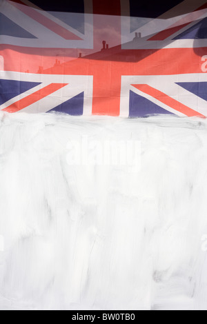 A Union Jack flag hangs above white emulsion paint which has been smeared over a shop window in Lavender Hill, Battersea - Stock Photo