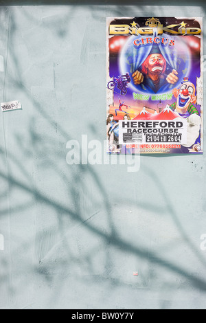 The sad face of a clown is seen on a circus poster next to a local pub advert that are pasted on a former high street - Stock Photo