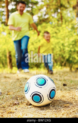 Image of ball on ground in park with running father and son at background - Stock Photo