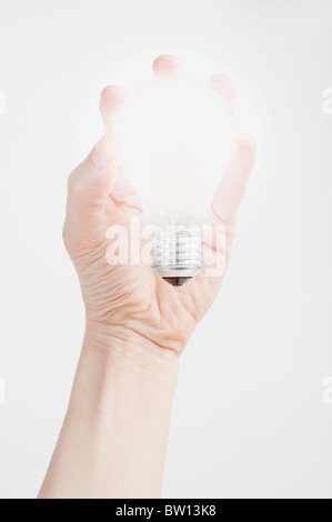 Hand holding a glowing light bulb - Stock Photo