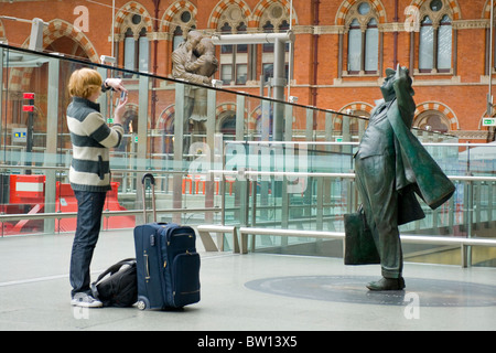 St Pancras Station , young traveler or tourist takes photo of statue of Sir John Betjeman on upper causeway by Eurostar - Stock Photo