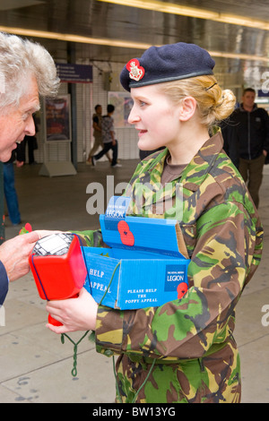 Kings Cross Station young teenage pretty girl army cadet fatigues selling Remembrance Armistice poppy Day Appeal - Stock Photo