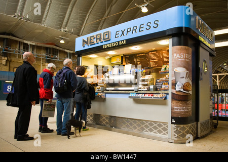 Kings Cross Station , Cafe Nero Express espresso coffee bar or kiosk with customers queuing by platforms - Stock Photo