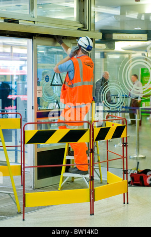 Kings Cross Station , engineer or man in orange overalls uniform at work repairing door surrounded by yellow & black - Stock Photo